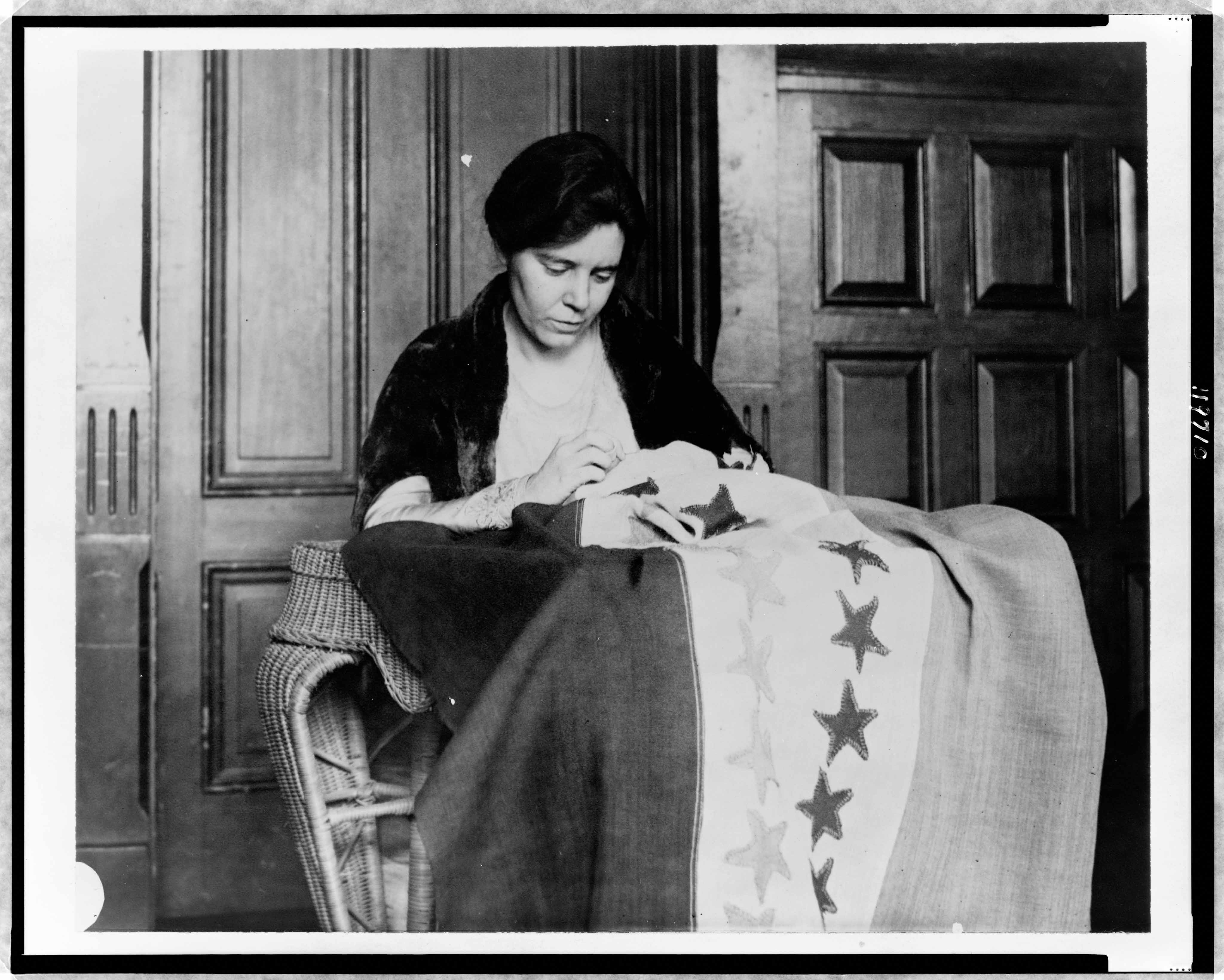 A photo of Alice Paul sewing suffrage flag.