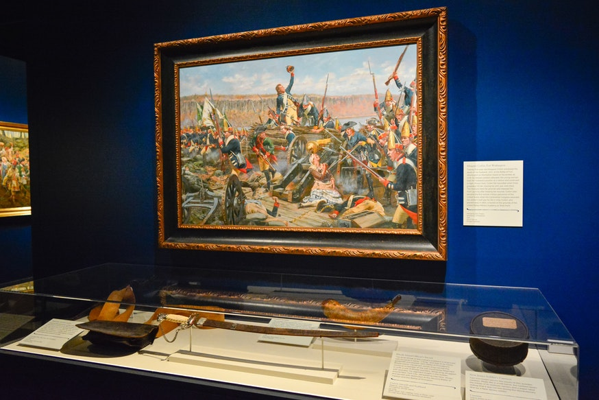 A painting hangs above a display case of corresponding artifacts in the Liberty exhibit.