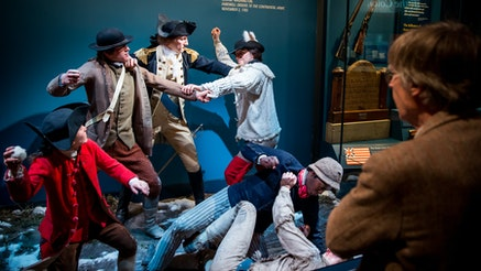 A visitor looks at a tableau scene depicting George Washington breaking up a fight among his troops in Harvard Yard.