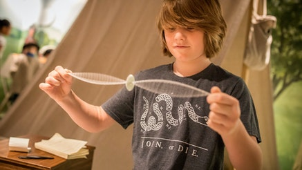 A white adolescent male plays with a Revolutionary-style whirligig.