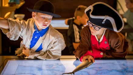 Two male adolescents interactive with a digital map in Revolution Place. They are both dressed in Revolutionary-era clothing.