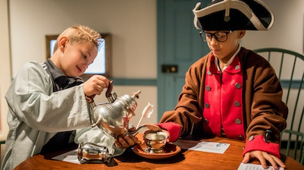 Two white male adolescents, both standing at a wooden table, interact with a play tea set. The adolescent on the left is pretending to pour tea into a silver teacup from a silver teapot. The adolescent on the right has his hand on the teacup saucer. Both are dressed in Revolutionary-era outfits.