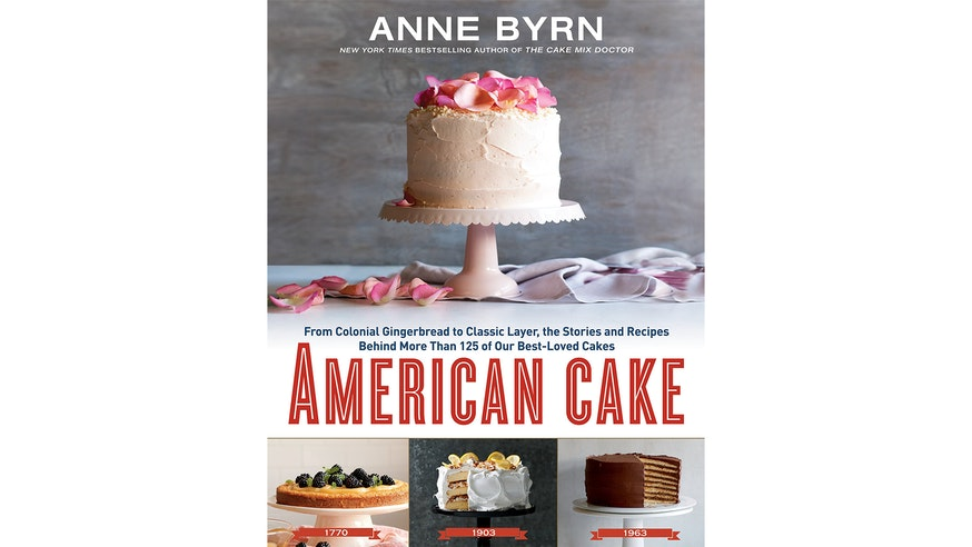 This image depicts the book cover of American Cake by Anne Byrn. The book cover shows a white frosted cake with pink rose petals on top. The cake sits on a white cake stand with more petals surrounding the right side of the stand. Below this image is the title of the book. Below the title of the book are three smaller photographs of cakes dated 1770, 1903, and 1963.