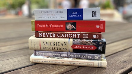 200th Edition Museum Staff Picks Reading List includes A People's History of the American Revolution by Ray Raphael; John Adams by David McCullough; Never Caught by Erica Armstrong Dunbar; American Revolutions: A Continental History 1750-1804 by Alan Taylor; The Shoemaker and the Tea Party by Alfred F. Young; and Spies in the Continental Capital by John A. Nagy. The books are stacked on top of one another on a wooden bench outside on a sunny day. The books and the bench are in clear view while the background is blurred.