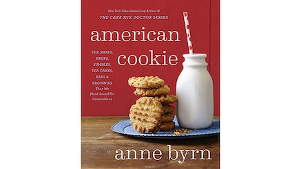 This image depicts the book cover of American Cookie by Anne Byrn. There is a stack of peanut butter cookies and a glass of milk with straw. The milk and cookies are on a blue plate on a wooden table with a red background.