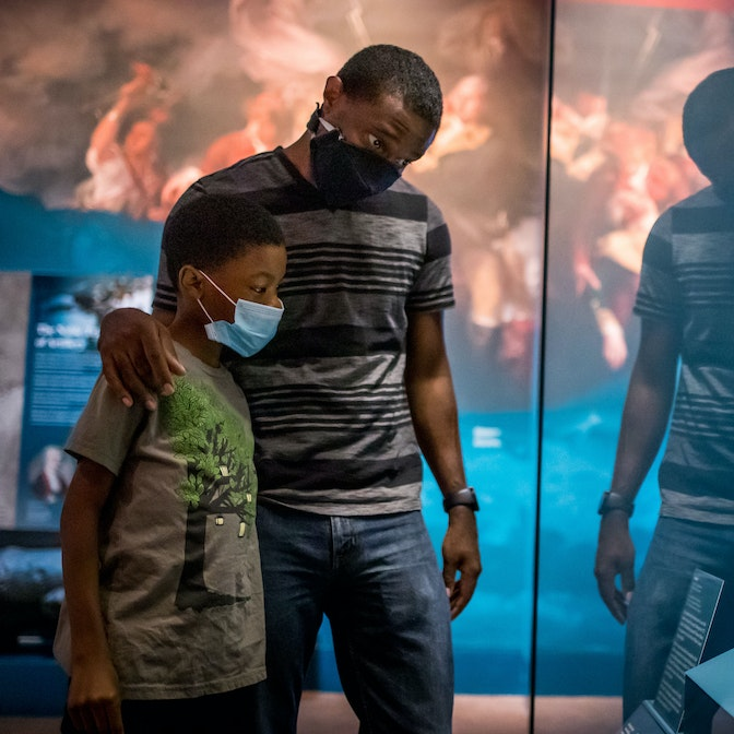 A father and son, both wearing masks, inspect one of the many rifles on display in the galleries.