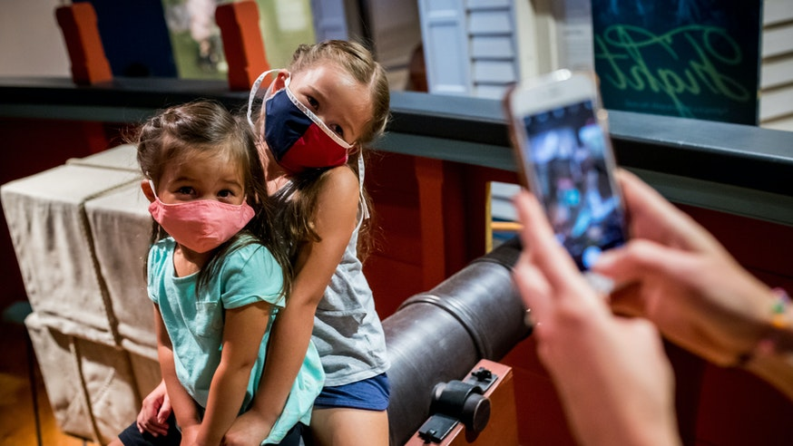 A mother takes a picture of her two young daughters, all wearing masks, on one of the cannons of the Privateer Ship in the galleries.