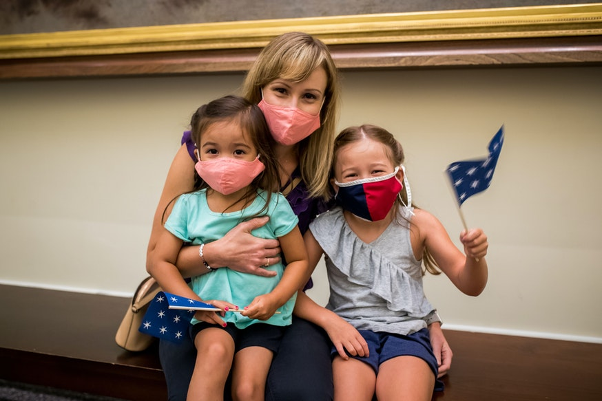 A mother and her two young daughters, all wearing masks, wave a 13-star flag while sitting on a bench in the Museum.