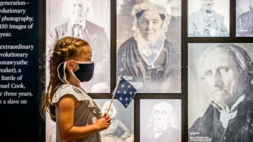 A young, female visitor, wearing a mask and holding a 13-star flag, admires photographs in the Museum's galleries.