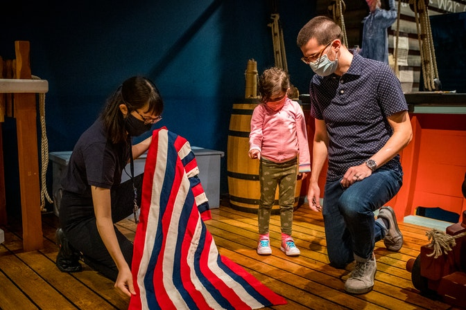 A masked Museum worker displays a flag to a father and daughter on the Privateer Ship in the galleries.
