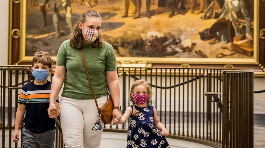 A masked family walks in front of The Siege of Yorktown painting located outside the galleries.