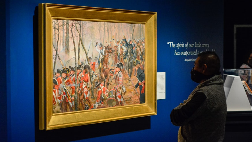 A Museum staff member views a painting in the Liberty exhibit