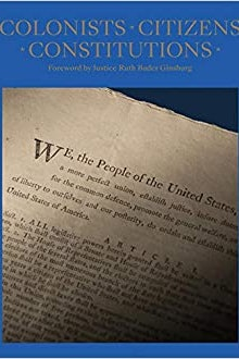 """The image depicts Colonists Citizens Constitutions book cover by James Hrdlicka. It is a blue cover with a photo of the first few lines of the constitution. """"We, the people of the United States,"""" is a visible."""