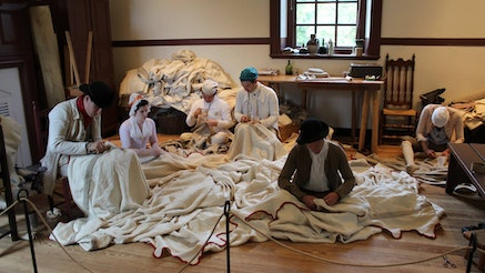 Staff members from the Museum of the American Revolution and Colonial Williamsburg work on sewing the Museum's replica of George Washington's headquarters tent