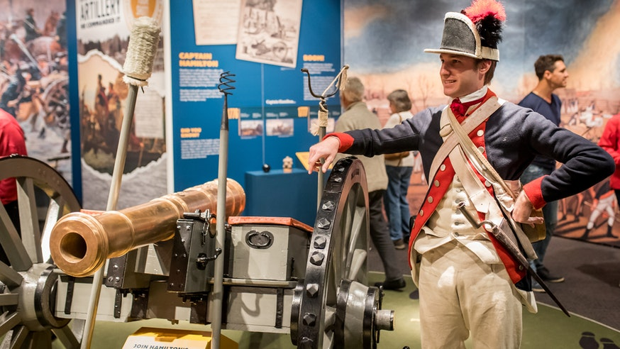 A male costumed Museum educator gives a demonstration about a cannon as part of the Hamilton Was Here exhibit.