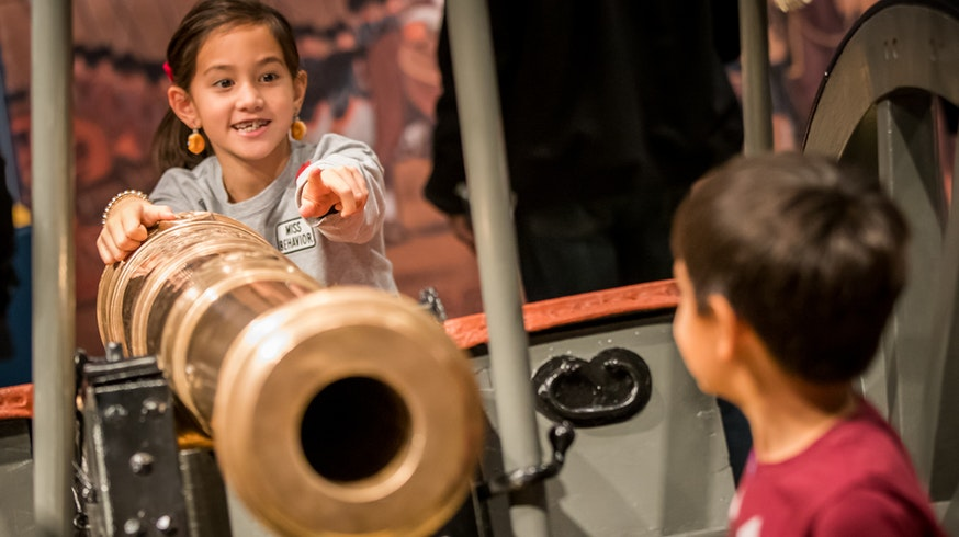 A brother and sister interact with a prop cannon in the Hamilton Was Here exhibit.