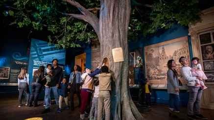 The Boston Liberty Tree is in the middle of the Becoming Revolutionaries gallery. Guests explore the gallery.
