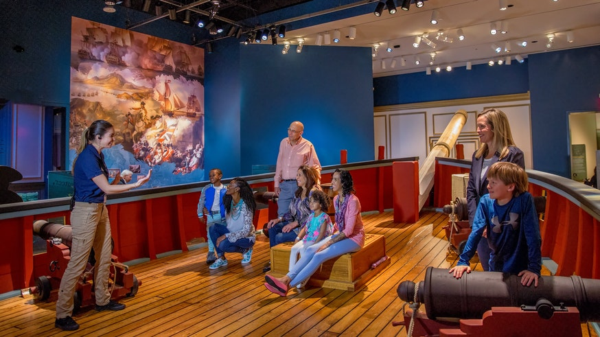 A visitor engagement associate educates families on the Privateer Ship in the galleries.