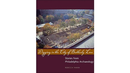 This image depicts the book cover of Digging in The City of Brotherly Love by Rebecca Yamin. The cover is a photo of a Philadelphia park in the fall. The top and bottom of the book cover are purple. The title of the book is written in front of a yellow strip.